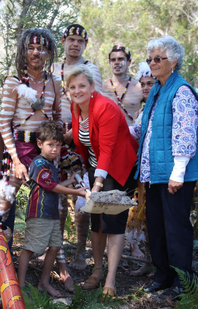 Yokarrah Walker helps Mayor Karen Williams turn sod for the Minjerribah fire trail project with Aunty Joan Hendriks and Yulu Burri Ba dancers.
